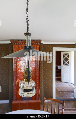 Kerosene lamp in a room with tiled stove - Stock Photo