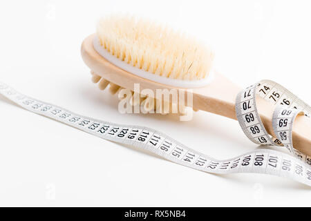 Dry massage brush with tape measure on white desk. Health and diet. Fitness concept. - Stock Photo