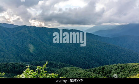 Mountain Ridge covered with forests in dense clouds. The main Caucasian ridge. Environmental Protection. Travel background. Caucasus, Russia - Stock Photo