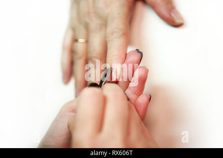 nail service manicurist makes an elderly woman with a metal tool - a lancet with a spatula at the end. Moving off the nail cuticle. reporting shooting - Stock Photo