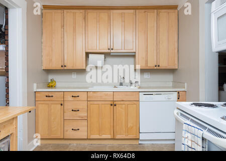 Clean light tan wood cabinets in small kitchen space - Stock Photo
