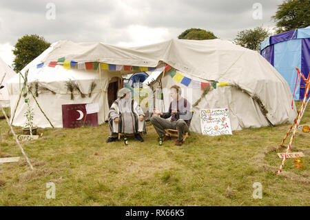 Two Masseurs share a conversation and a beer, Big Green Gathering, UK August 2005 - Stock Photo