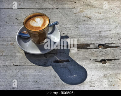 18 February 2019, Berlin: A café au lait decorated with a heart of milk foam called Cortado stands on the weathered wooden table of a café in the sun. The hot drink foamed in a glass is prepared in many cafés with sweetened condensed milk. Photo: Soeren Stache/dpa-Zentralbild/ZB - Stock Photo