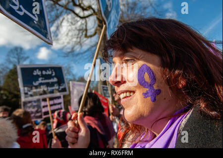 Brussels, North Brabant, Belgium. 8th Mar, 2019. A woman is seen wearing the female symbol painting in her face during the protest.On the 40th anniversary of the 5-days women's uprising against 'compulsory hijab order'' in 1979 in Iran. Women around several cities in Europe took the streets for 3 days on 6th, 7th, and 8th of March 2019, to resound the struggle of 'revolutionary women in 1979'' against compulsory hijab in Iran. In Brussels, a demonstration took place in front of the embassy of the Islamic Republic of Iran, after that they demonstrated also in front of the US embassy. - Stock Photo