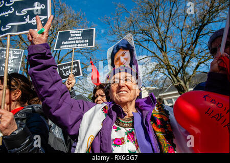 """An elderly woman is seen making the peace sign during the demonstration. On the 40th anniversary of the 5-days women's uprising against """"compulsory hijab order"""" in 1979 in Iran. Women around several cities in Europe took the streets for 3 days on 6th, 7th, and 8th of March 2019, to resound the struggle of """"revolutionary women in 1979"""" against compulsory hijab in Iran. In Brussels, a demonstration took place in front of the embassy of the Islamic Republic of Iran, after that they demonstrated also in front of the US embassy. - Stock Photo"""