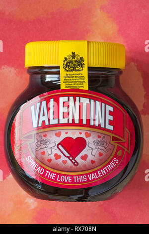 Special edition jar of Valentine Marmite by Unilever - spread the love this Valentines set on red patterned background - Stock Photo