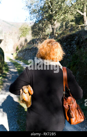 rear of middle aged french woman walking down a country path with fresh baguettes tucked under her arm and a bag on her right shoulder