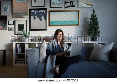 Woman relaxing with laptop on living room sofa - Stock Photo