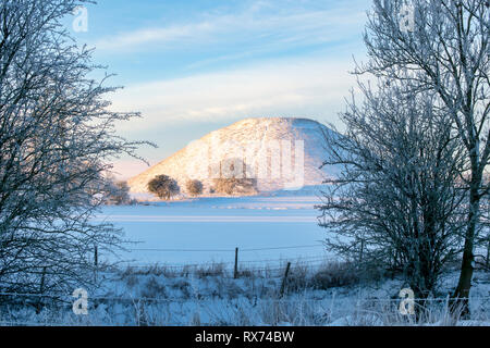 Silbury Hill in the winter snow just after sunrise. Avebury, Wiltshire, England - Stock Photo
