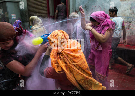 A group of young people have fun throwing colored powders and water during their participation in the Holi celebration. - Stock Photo