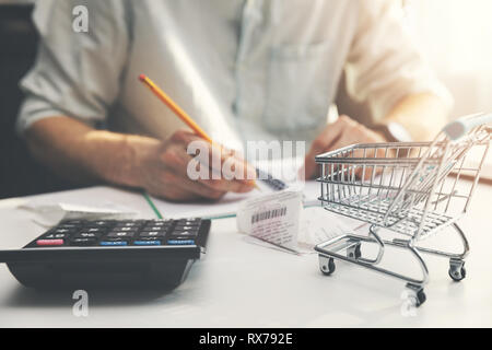 family budget planning - man counting and checking household daily expenses - Stock Photo