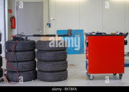 two stacks of car tires and a tool trolley - Stock Photo
