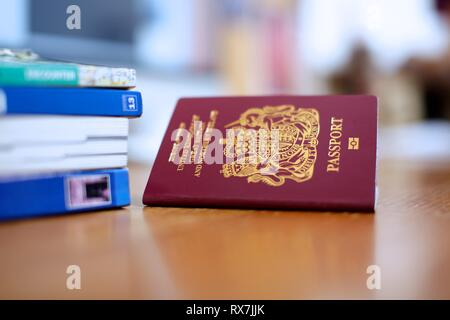 Side view of UK passport with travel guides - Stock Photo