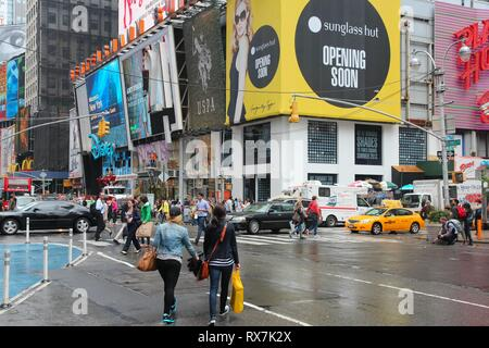 NEW YORK, USA - JUNE 10, 2013: People visit rainy Times Square, NY. Times Square is one of most recognized places in the world. More than 300,000 peop - Stock Photo
