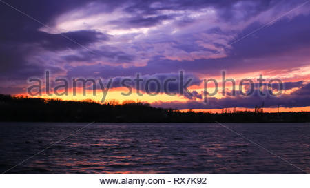 Cloudy storm approaching over a coast Wide shot on a lake with in the background the city at sunset - Stock Photo