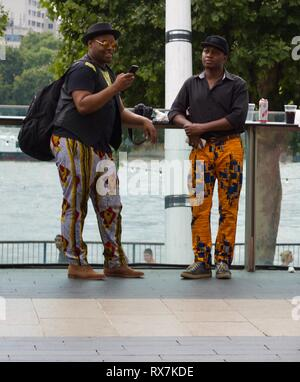 Two black men standing beside River Thames at Africa Utopia Festival on London's Southbank - Stock Photo
