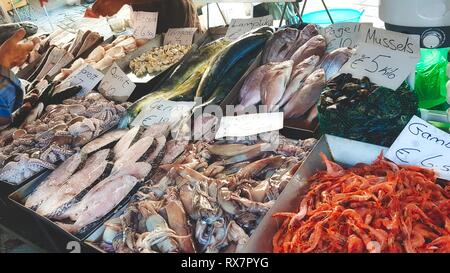 Varied fresh fish and seafood in trays at a fishmonger's stand in an open-air market - Stock Photo