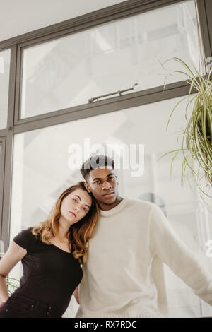 A good looking and young couple poses with next to each other and look at the camera. She is White, he is black  They have serious faces - Stock Photo