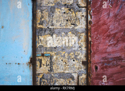 Blue and red painted metal doors in a brick and concrete rough wall forming a grungy abstract texture background - Stock Photo