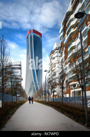 Young couple walking in the direction of the Hadid Tower of Citylife district, Milan, Italy - Stock Photo