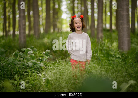 Cute little girl having fun in a poplar forest - Stock Photo