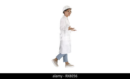 Full length shot. Side view. Woman engineer walkin and talking emotionaly on white background. Professional shot in 4K resolution. 006. You can use it - Stock Photo