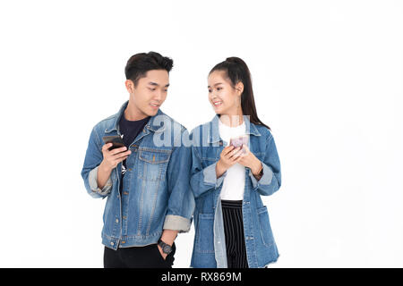 young Asian couple using smartphone on white background - Stock Photo