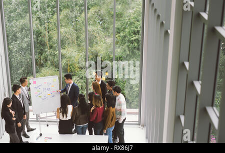 Businessman presenting at whiteboard Gruop of business people standing around white board during meeting in office - Stock Photo
