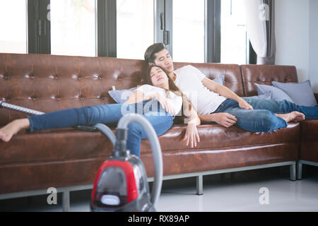 Man husband cleaning the house helping wife and Cleaning lady taking a nap on sofa after cleaning the whole room Tired couple together - Stock Photo