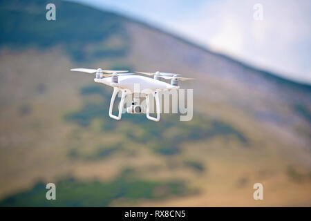 drone quadcopter with digital camera flying in nature - Stock Photo