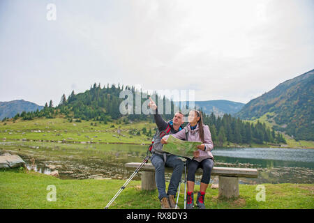 Hiking couple. Young couple with backpacks looking at the map beside lake - Stock Photo