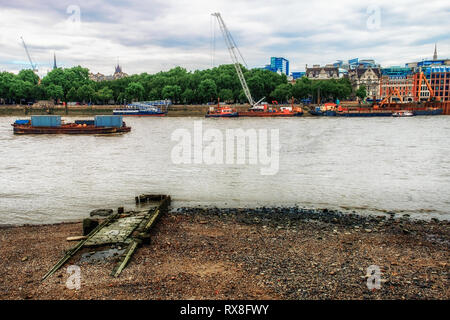 Derelict river taxi paved path on the South Bank of the river Thames at low tide,  facing North Bank under construction, London U.K - Stock Photo
