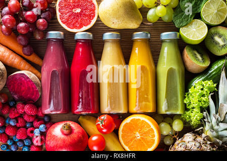 Colorful smoothies in bottles and fresh fruits and vegetables on wooden table, top view. - Stock Photo