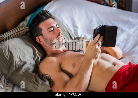 Handsome shirtless muscular man in bed typing on cell phone, sending text message or dialing number or reading web pages - Stock Photo