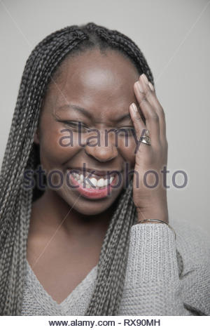 Portrait carefree beautiful young African American woman with long black braids laughing - Stock Photo