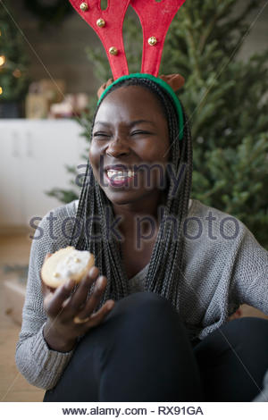 Happy young woman in christmas reindeer antlers eating cookie - Stock Photo