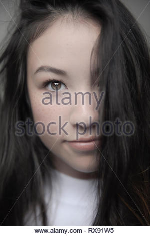 Close up portrait confident beautiful brunette teenage girl with brown eyes and freckles - Stock Photo