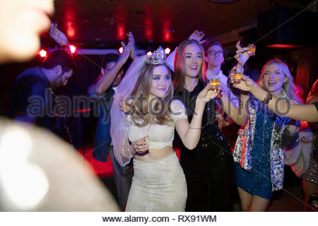 Bachelorette and friends dancing and drinking in nightclub - Stock Photo