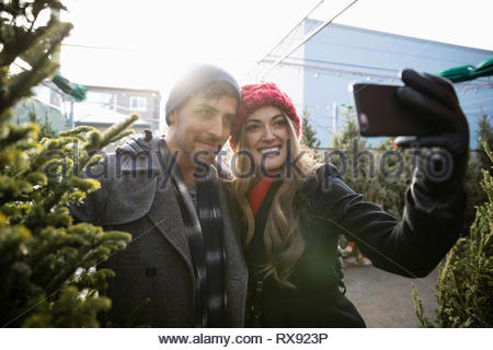 Happy couple taking selfie with christmas tree at christmas market - Stock Photo