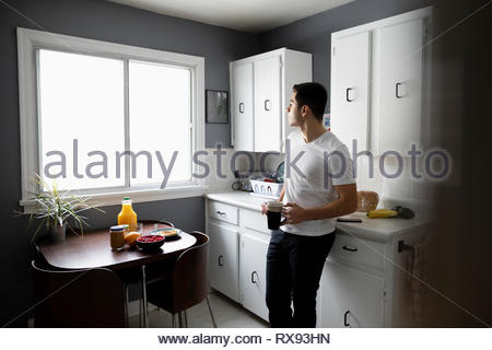 Thoughtful young Latinx man drinking coffee in morning kitchen - Stock Photo