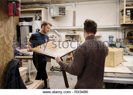 Male carpenters carrying table in workshop - Stock Photo