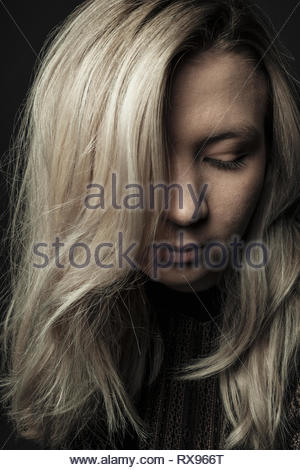 Close up portrait beautiful young woman with blonde hair looking down - Stock Photo