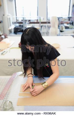 Female fashion designer cutting pattern in studio - Stock Photo