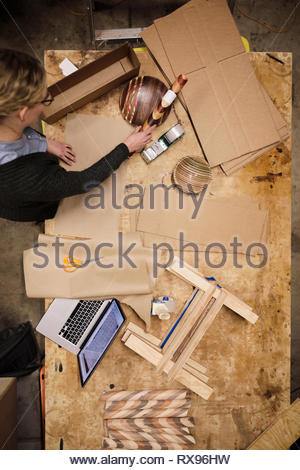 View from above female artist wrapping wooden crafts in workshop - Stock Photo