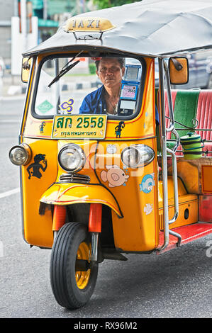 Bangkok, Thailand: Close-up front view of a yellow painted Tuk-tuk with a mid age male driver, isolated from other traffic - Stock Photo