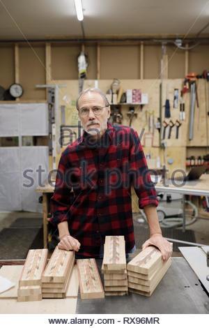 Portrait confident senior carpenter in workshop - Stock Photo