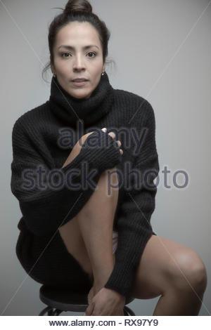 Portrait confident beautiful Latina woman wearing sweater dress - Stock Photo