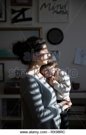 Serene mother holding toddler daughter - Stock Photo