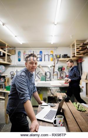 Portrait confident male artist working in woodworking workshop - Stock Photo