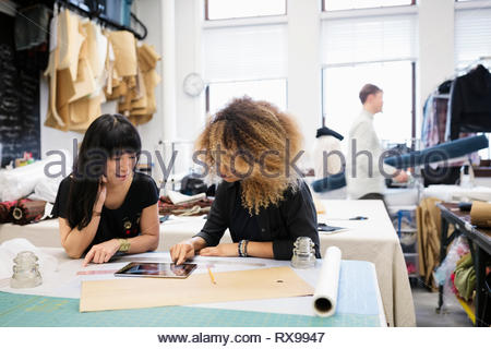 Female fashion designers using digital tablet in studio - Stock Photo